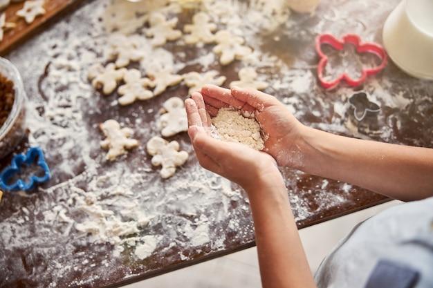 Две руки кладут муку на стол с печеньем