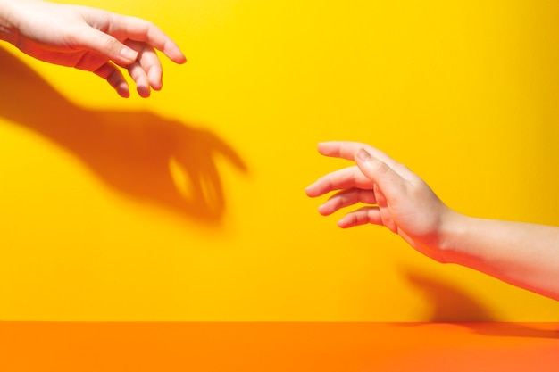 Two hands reach for each other with fingers. shadows and hard light