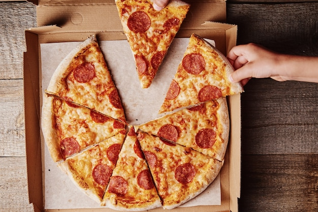 Two hands takes slices of pizza from a cardboard box, top view