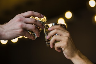 Two hands toasting whiskey against illuminated backdrop