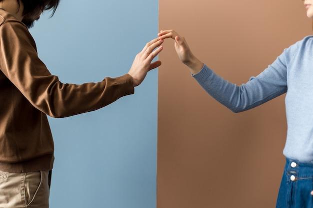 Две руки касаются друг друга кончиками пальцев на разном фоне.