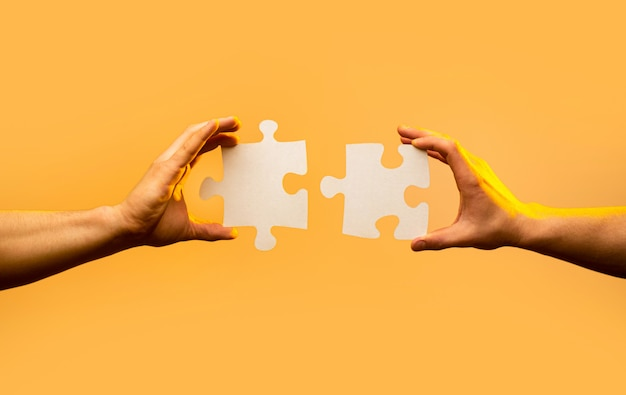 Two hands trying to connect couple puzzle piece on yellow background