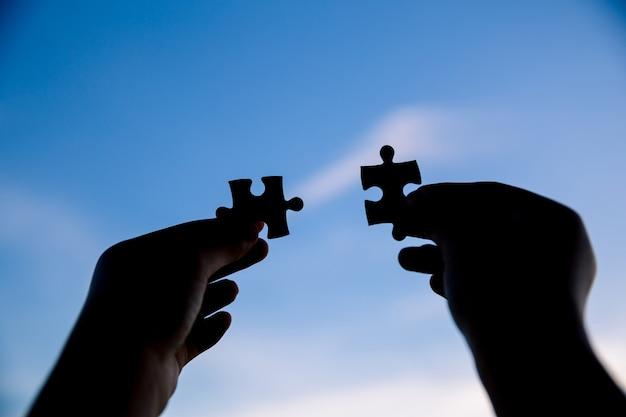夕日を背景にカップルパズルのピースを接続しようとする2つの手。