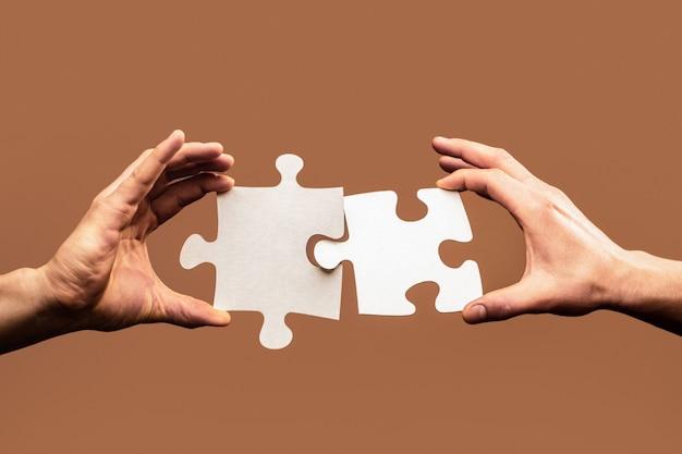 갈색 벽에 몇 퍼즐을 연결하려고 두 손. 지 그 소 퍼즐을 연결하는 사람의 손을 닫습니다. 비즈니스 솔루션, 성공 및 전략 개념.