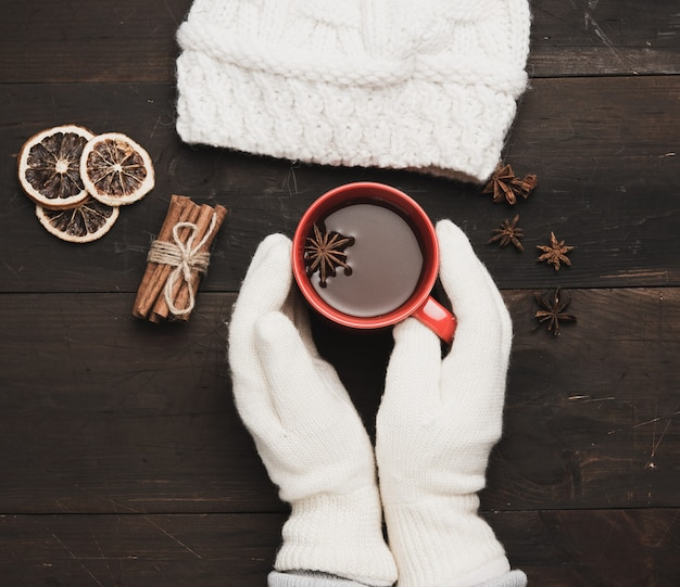 Two hands in white knitted mittens hold a red cup with a drink on a brown wooden table, top view