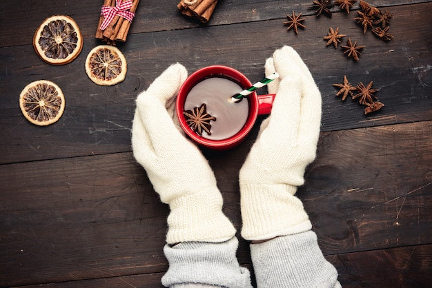 Two hands in white knitted mittens hold a red cup with a drink on a brown wooden table