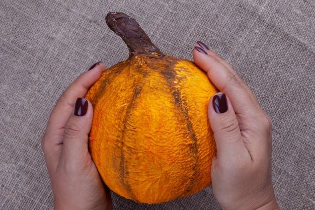 茶色のマニキュアを持った両手は、黄麻布の表面にハロウィーンのための自家製のオレンジ色の張り子のカボチャを持っています