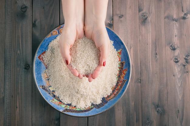 Две руки с рисовыми зернами над тарелкой