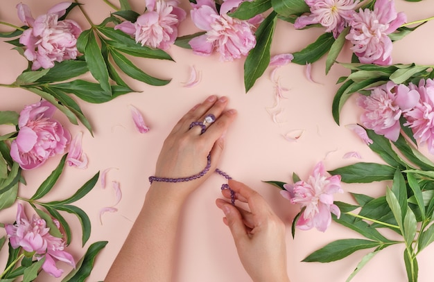 Two hands of a young girl with smooth skin and a bouquet of pink peonies on a peach surface