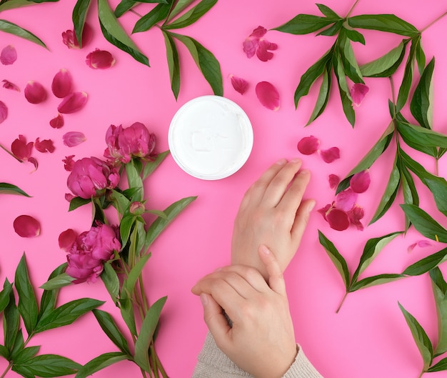 Two hands of a young girl with smooth skin and a jar with thick cream and burgundy flowering peonies