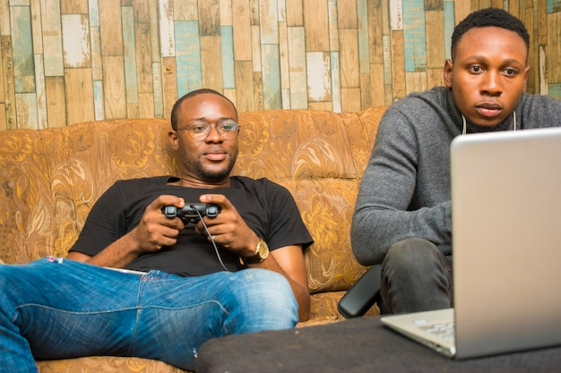 Two handsome africans guys sitting on the couch playing video games with joystick, game pad, pad