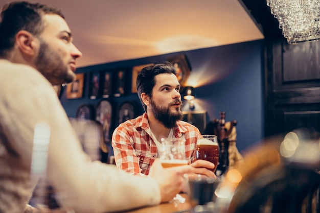 Two handsome bearded man drinking beer in pub