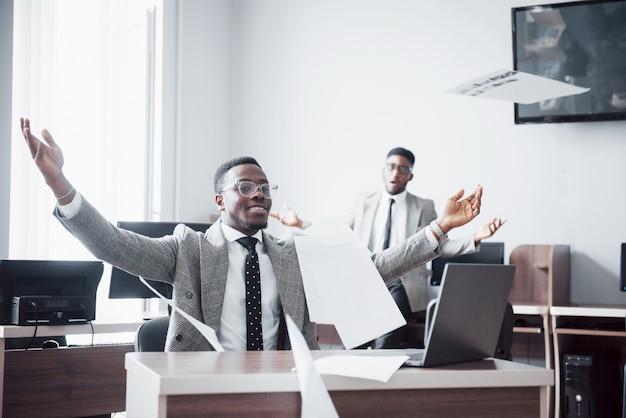 Красивое жизнерадостное торжество бизнесмена афроамериканца 2 успешное с бросать бумагу в рабочем месте