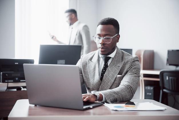 ワークスペースオフィスで2つのハンサムな陽気なアフリカ系アメリカ人エグゼクティブビジネス男