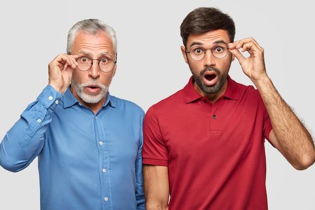Два красавца-отца и солнышко замечают нечто невероятное, смотрят сквозь круглые очки, одетые в яркую стильную одежду, изолированно над белой стеной. удивленные бородатые зрелые и взрослые мужчины