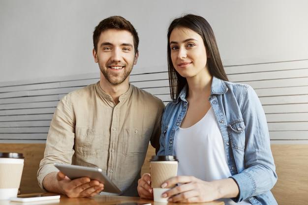 Два красивых фрилансера сидят в коворкинг-пространстве, пьют кофе и говорят о командном проекте. мужчина и женщина, улыбаясь, позирует для статьи.