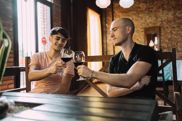 レストランでグラスワインで乾杯する2人のハンサムな友人。