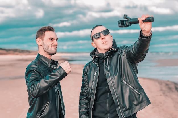 Двое красивых друзей-мужчин делают селфи с помощью камеры действия со стабилизатором карданного подвеса на пляже.