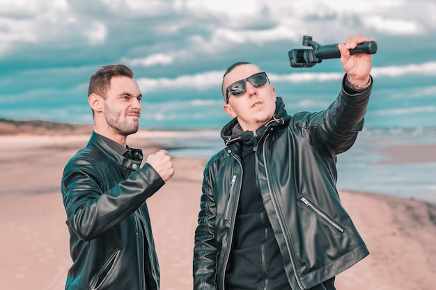 Two handsome male friends making selfie using action camera with gimbal stabilizer at the beach.