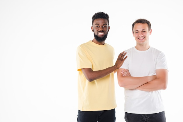 Two handsome men smiling and posing together on camera with thumb up isolated over white wall