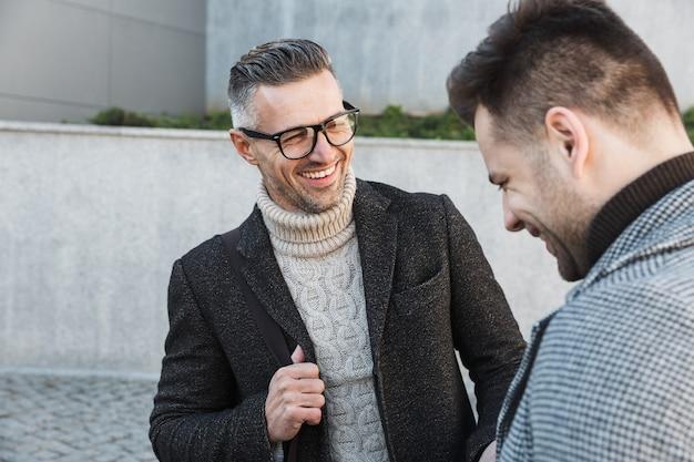 コートを着て屋外で時間を過ごし、話している2人のハンサムな男性