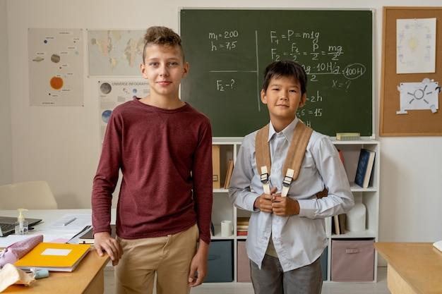 교실에서 당신을 바라보는 평상복을 입은 두 명의 잘생긴 남학생