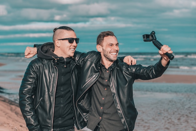 Two handsome smiling friends making selfie using action camera with gimbal stabilizer at the beach.