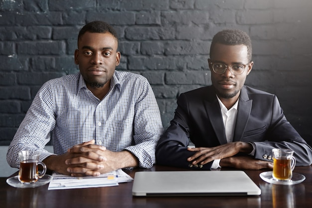 Two handsome successful afro-american businessmen working in office sitting at table with laptop, papers and mugs