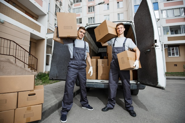 箱だらけのバンの前に制服を着た2人のハンサムな労働者が立っている