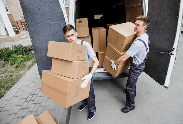 制服を着た2人のハンサムな労働者が箱でいっぱいのバンを降ろしています