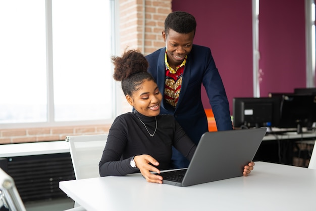 Two handsome young african men and women at the table with laptop at work