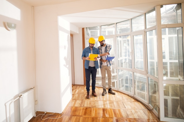 安全帽子をかぶった2人のハンサムな若いエンジニアが、非常に大きな建物の窓の近くにあるフォルダーの設計図を指摘することで、お互いにアイデアを説明しています。