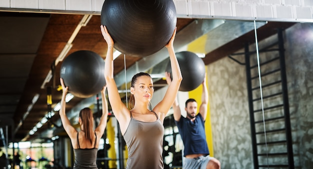 Two handsome young people using pilates balls for exercising in a gym.