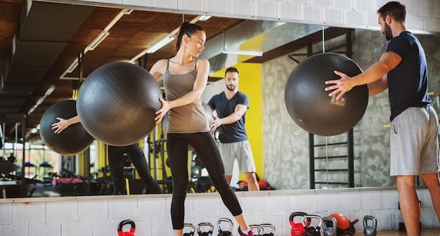 ピラティスボールを使用してジムで運動する2人のハンサムな若者。