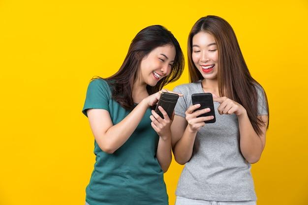 Два счастья азиатской улыбающейся молодой женщины-геймера, использующей смарт-мобильный телефон и играя в игры