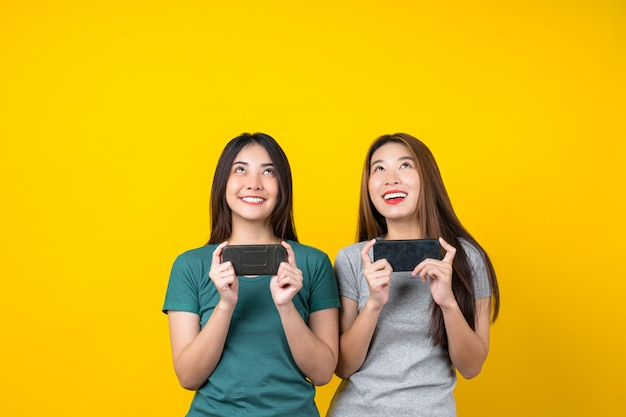 Two happiness asian smiling young woman gamer using smart mobile phone and playing games on isolated yellow color wall