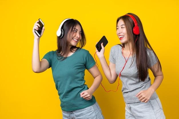 音楽を聴くためのワイヤレスヘッドフォンを身に着けている2つの幸福アジアの笑顔の若い女性