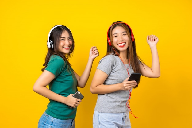 Two happiness asian smiling young woman wearing wireless headphones for listening music via smart mobile phone and dancing on isolated yellow wall, lifestyle and leisure with hobby concept