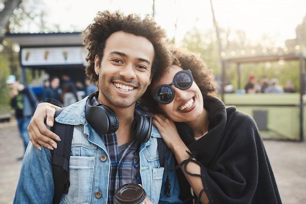 アフリカ系アメリカ人の2人の幸せな旅行者が、アフロのヘアスタイルを抱いてカメラを見て、公園を歩きながら写真を撮り、前向きな感情を表現します。