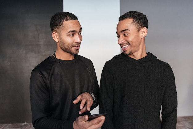 Two happy african young men standing and using cell phone