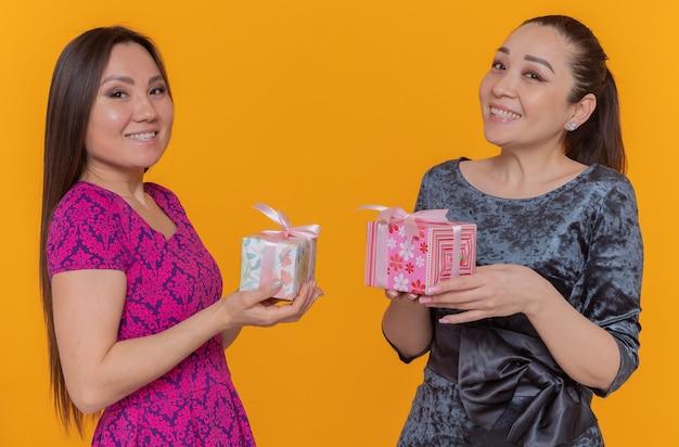 オレンジ色の壁の上に広く立って笑顔のプレゼントを開催する国際女性の日を祝う2人の幸せで陽気なアジアの女性