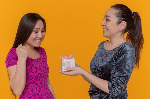オレンジ色の壁の上に立っている彼女の驚いた親友にプレゼントを与える国際女性の日女性を祝う2人の幸せで陽気なアジアの女性