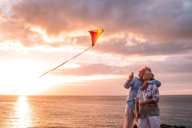 2명의 행복하고 쾌활한 노인은 일몰과 바다를 배경으로 해변에서 날아다니는 연을 가지고 노는 것을 즐기고 야외 활동적인 생활 방식을 취하는 사람들