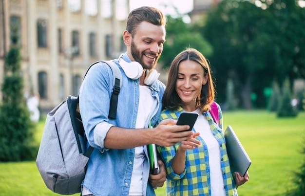 Два счастливых и взволнованных друга-студента с рюкзаками и смартфоном разговаривают и гуляют на свежем воздухе. красивая пара после уроков в университете