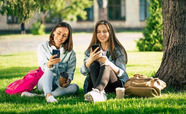 カジュアルなデニムの服を着た2人の幸せで興奮した学生のガールフレンドは、スマートフォンを持って大学の公園でリラックスして楽しんでいます。