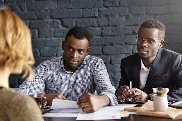 Два счастливых и дружелюбных темнокожих бизнесмена внимательно слушают ответы кандидата-женщины