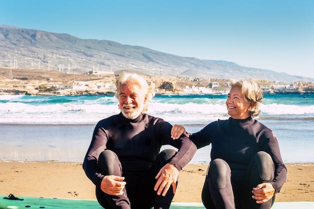 여름과 휴가를 함께 즐기는 두 명의 행복하고 재미있는 노인들이 서핑보드를 들고 땅에 앉아 잠수복을 입고 - 야외에서 쾌활한 연금 수령자