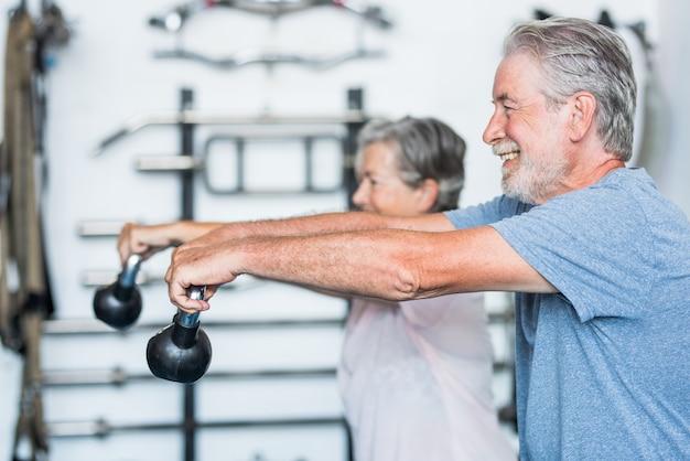 Два счастливых и зрелых активных пожилых и здоровых человека делают упражнения в тренажерном зале вместе, поднимая небольшую гантель - пенсионеры женщина и мужчина веселятся