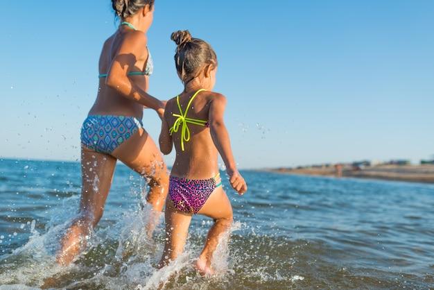 두 명의 행복하고 긍정적 인 여동생이 햇볕이 잘 드는 더운 여름날 휴가 기간 동안 파도를 따라 달리고 있습니다. 해외 가족 휴가 개념. copyspace