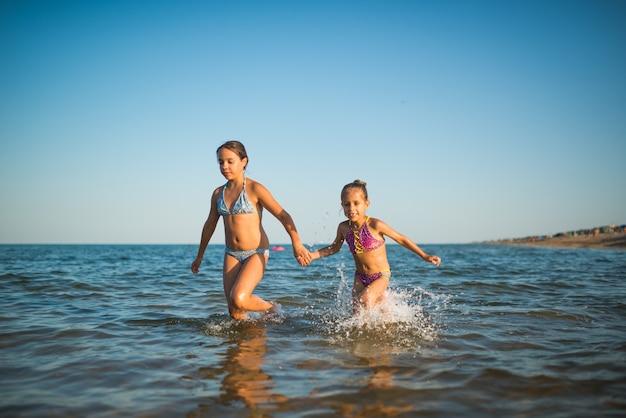 2人の幸せで前向きな女の子の姉妹が休暇中に海の波に沿って走ります